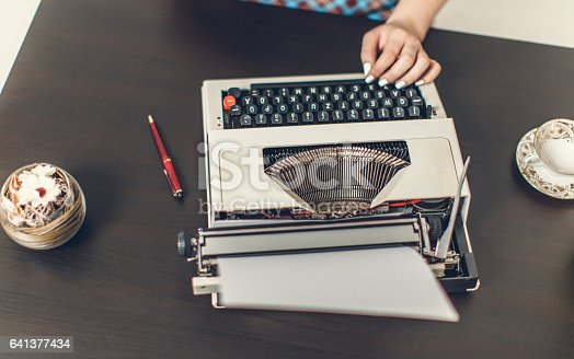 471445335istockphoto Pin Up girl with typewriter 641377434