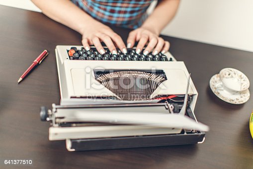 471445335istockphoto Pin Up girl with typewriter 641377510
