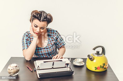 471445335istockphoto Pin Up girl with typewriter 641746836