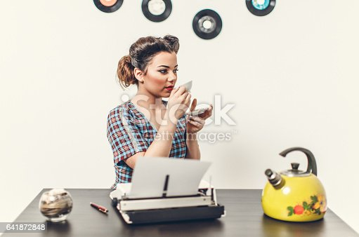 471445335istockphoto Pin Up girl with typewriter 641872848