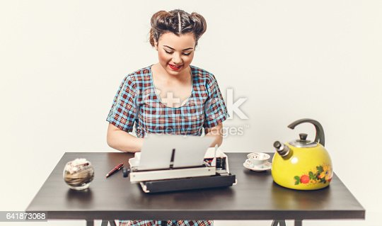 471445335istockphoto Pin Up girl with typewriter 641873068