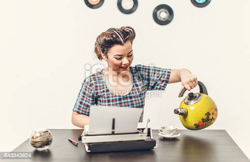 471445335istockphoto Pin Up girl with typewriter 643343624