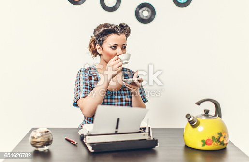 471445335istockphoto Pin Up girl with typewriter 654626782