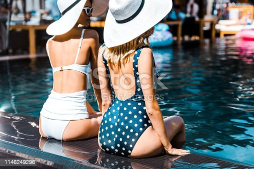 pin up girls in swimsuits and hats sitting at poolside
