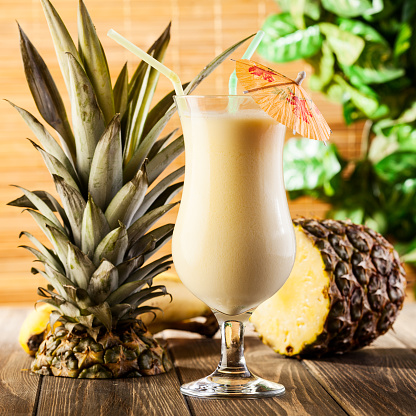Pina Colada On Wooden Background Garnished Pineapple Stock Photo - Download Image Now