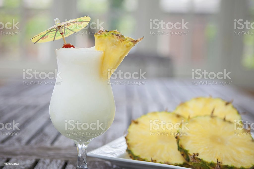 Pina colada with pineapple slices on wooden table stock photo