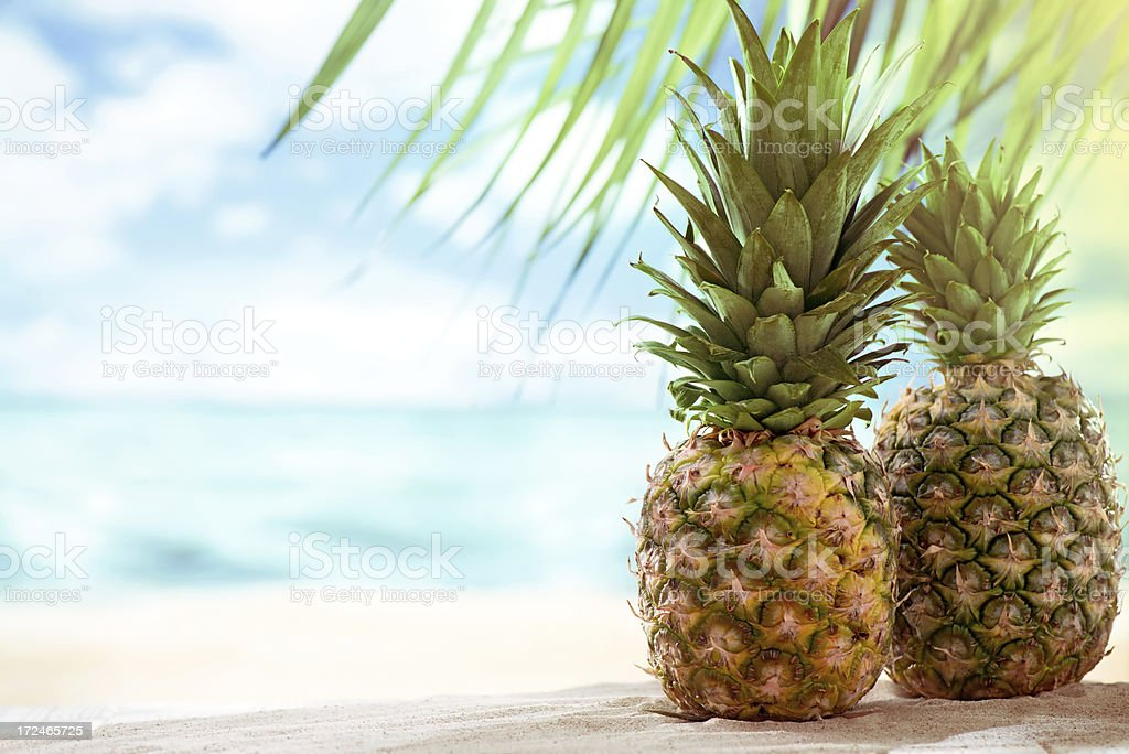 Pinapples on the beach with copy space stock photo