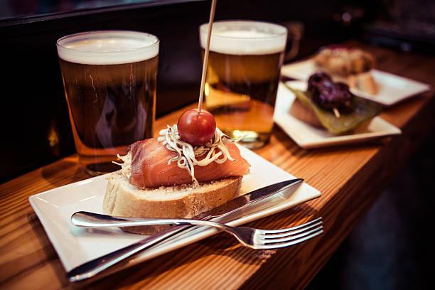 pinchos aus dem baskenland mit bier serviert - tapas stock-fotos und bilder