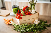 Wooden crate full of colorful fresh vegetables and fruits on a kitchen counter. Carrots, mushrooms, cherry tomatoes, asparagus, pepper, lettuce, zucchini, bananas