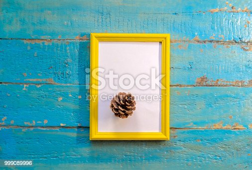 istock pine cone lies a yellow frame with a white background 999089996
