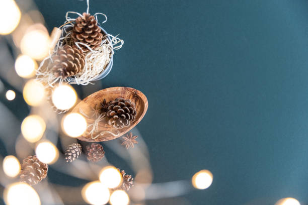 pine cones and Christmas lights on a teal background stock photo