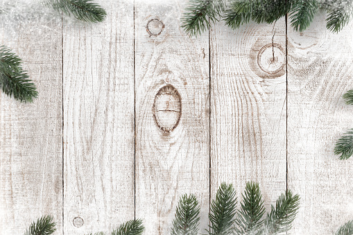 Pine leaves decorated as a frame on a white wooden background  with snowflakes. Merry Christmas and winter holiday background.
