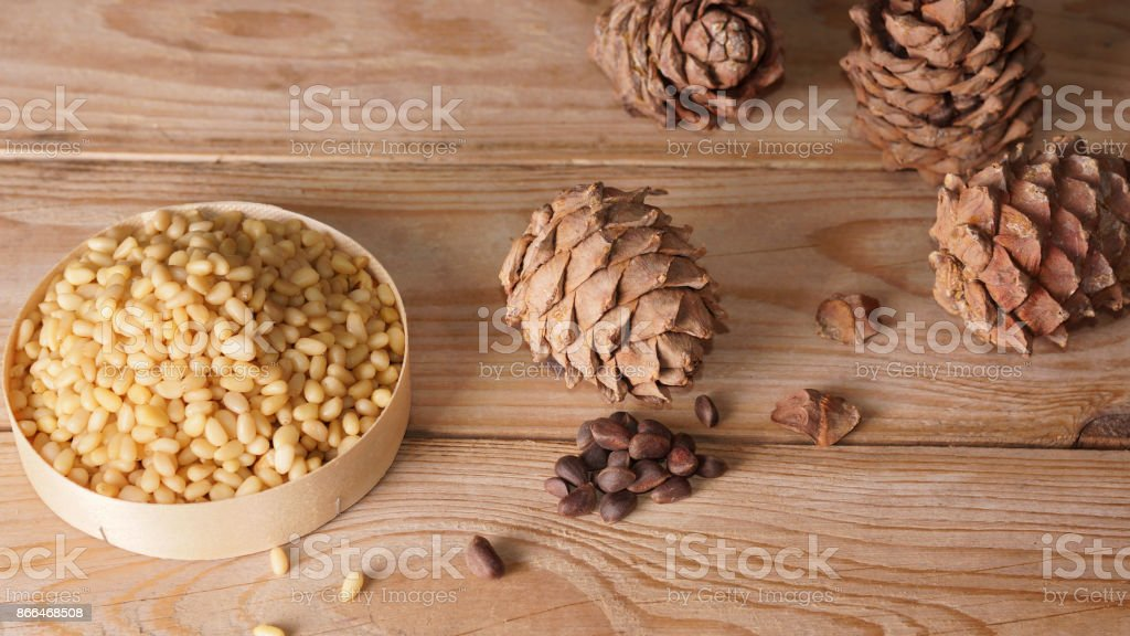Pine nuts and cedar cones are on a wooden table stock photo