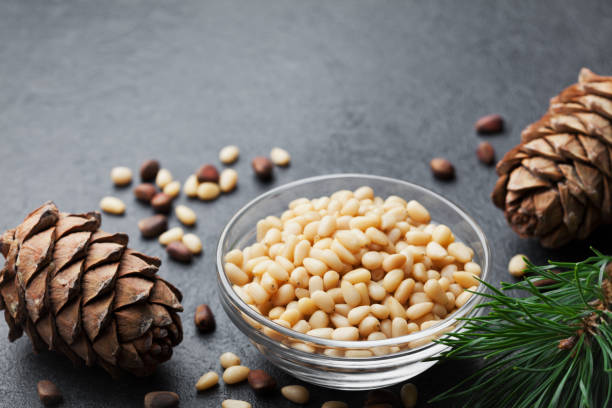 Pine nuts and cedar cones on black table. Organic and healthy superfood. Copy space for text. stock photo
