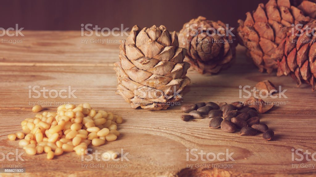 Pine nuts and cones on a wooden table stock photo