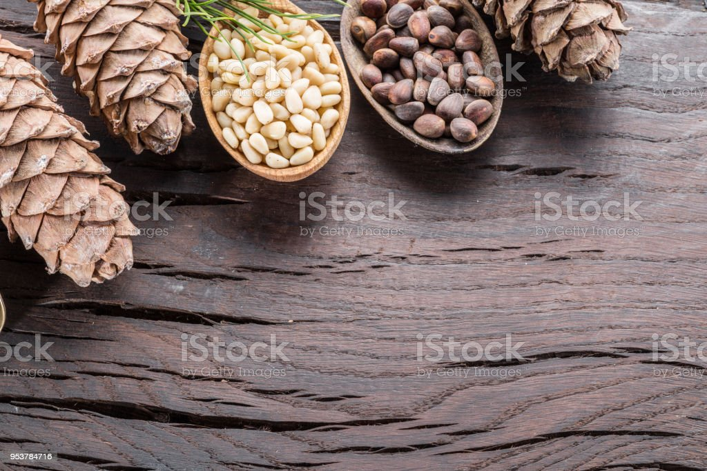 Pine nuts in the spoon and pine nut cone on the wooden table. Organic...