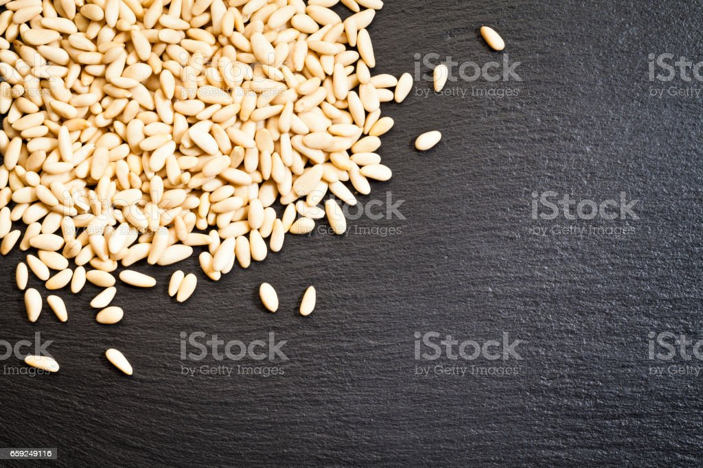 Pine nuts on dark slate table stock photo
