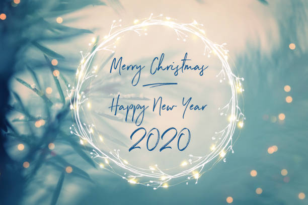 Pine tree background for Christmas Decoration with light garland and New Year greetings 2020 stock photo