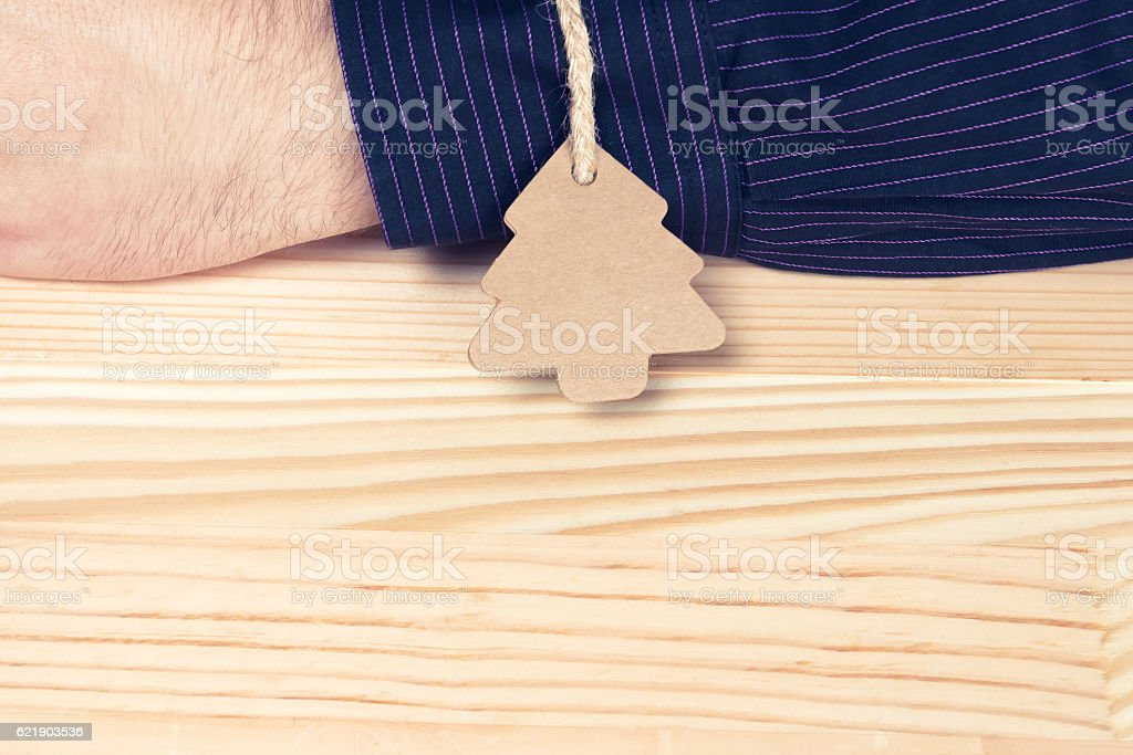 Pine tree shaped label tied with twine to an elegant man or...