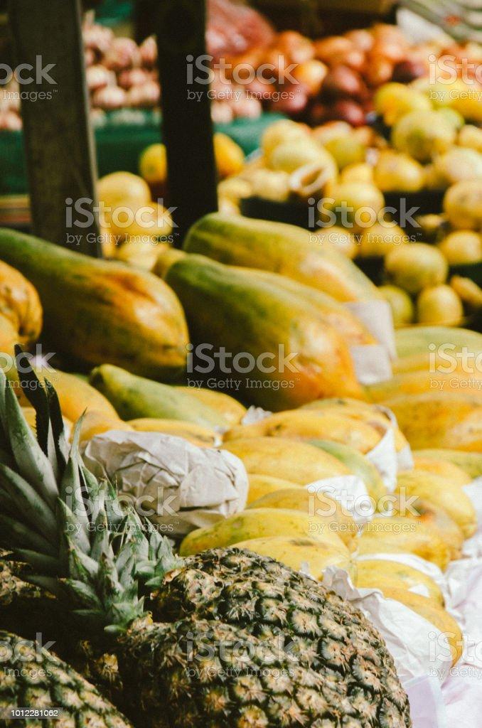 abacaxi e mamão expostos na tenda do mercado livre - foto de acervo