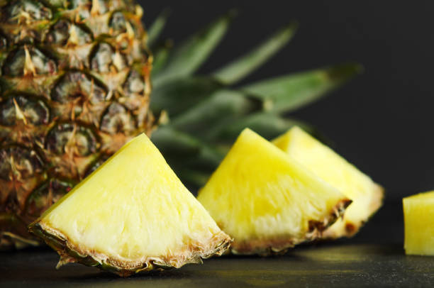 Pineapple and pineapple slices on black background. Delicious, juicy, dietary, summer fruit. stock photo