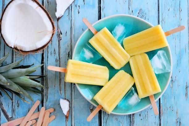 pineapple coconut popsicles, top view scene on blue wood - picolé imagens e fotografias de stock