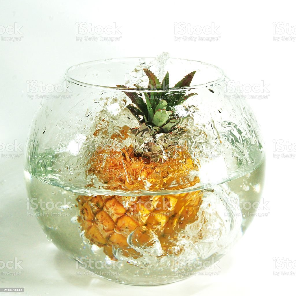Pineapple falling into water glass stock photo