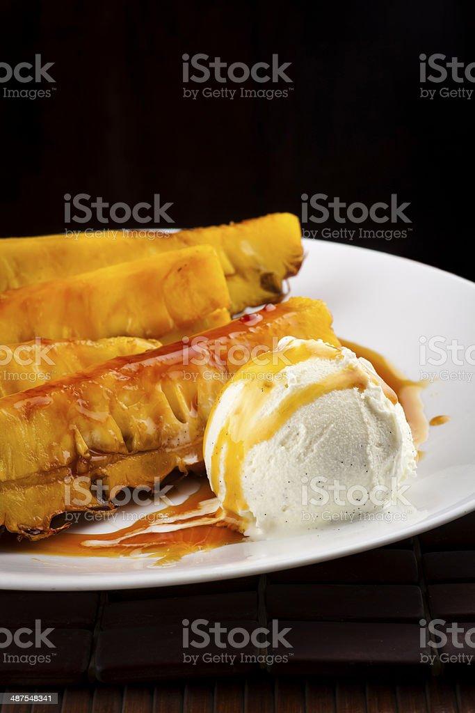 Pineapple fried in caramel sauce with  vanilla ice cream stock photo