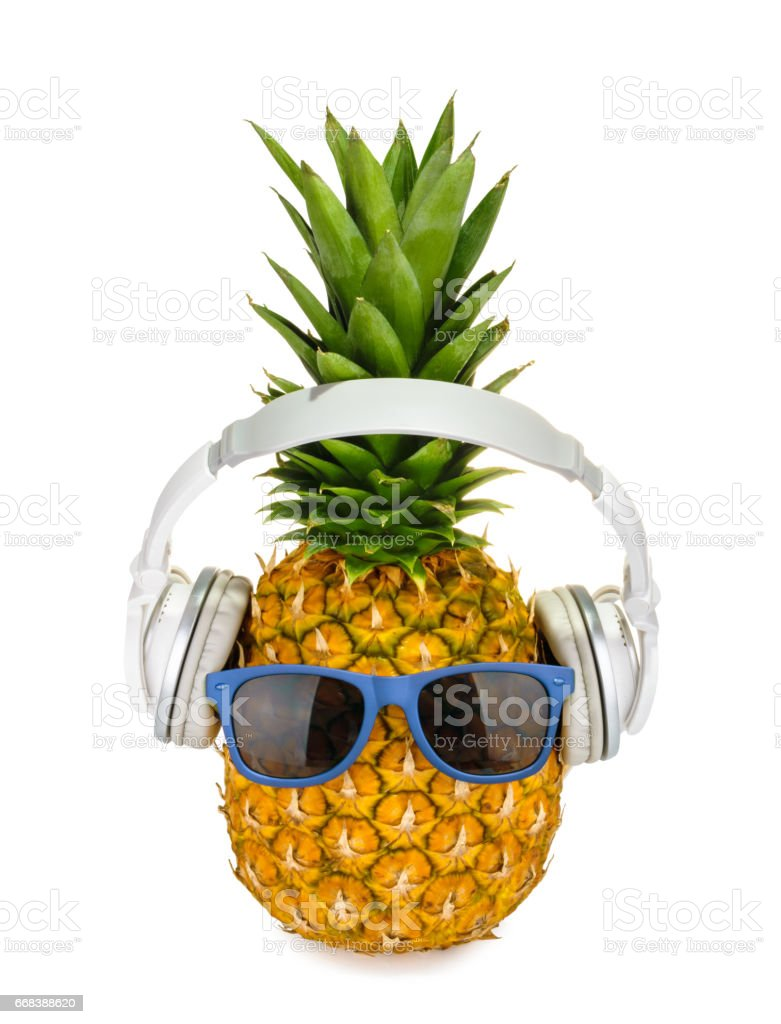 Pineapple fruit in a glasses with headphone isolated - Photo