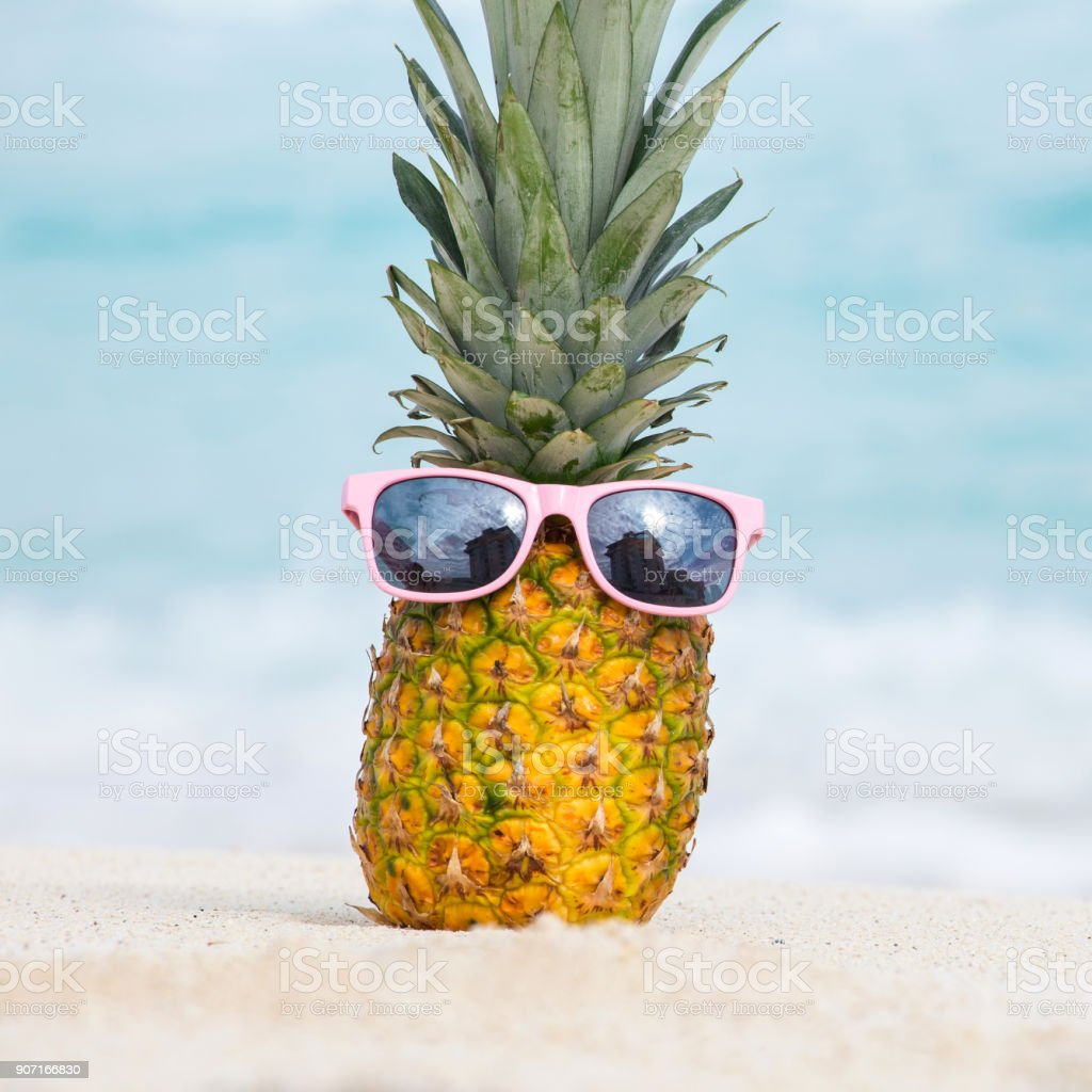 Pineapple fruit in sunglasses on sand against turquoise caribbean sea water stock photo