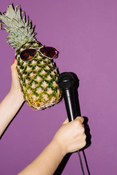 pineapple in earphones hand with microphone - hand holding phone zdjęcia i obrazy z banku zdjęć
