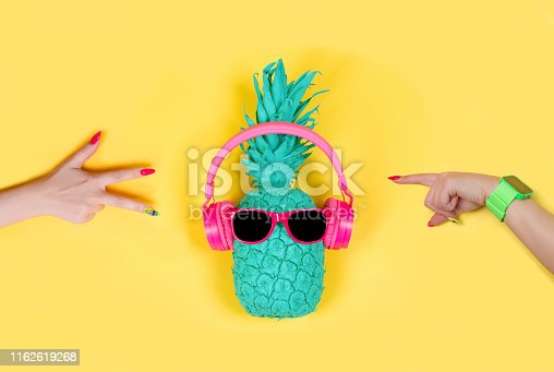 istock Pineapple in pink headphones and glasses 1162619268