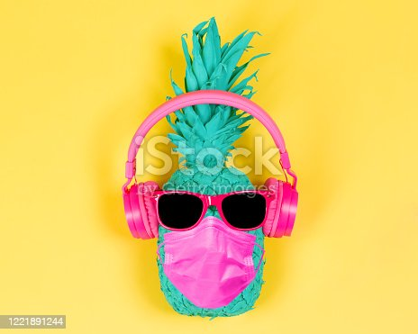 Pineapple in pink headphones and medical mask on a yellow background