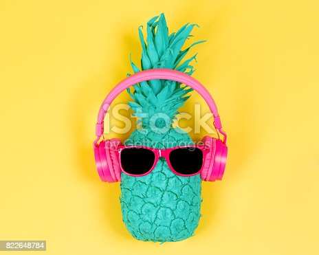 istock Pineapple in pink headphones 822648784