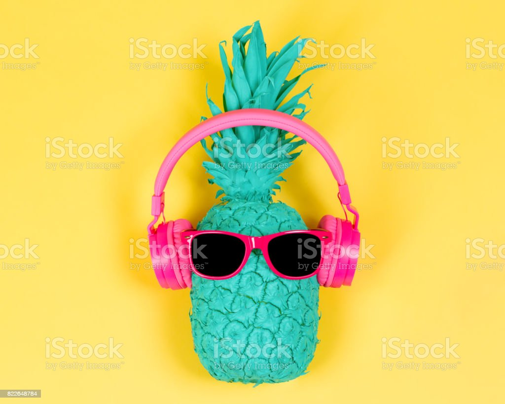Pineapple in pink headphones stock photo