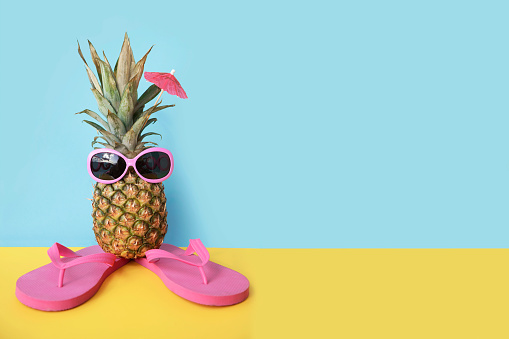 Pineapple in sunglasses and flip flops