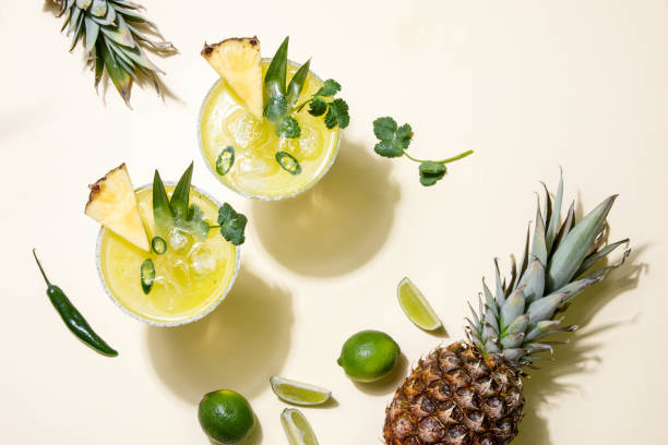 Pineapple jalapeno margarita summer cocktail Pineapple jalapeno margarita alcoholic cocktail in two glasses served under the summer sun light, view from above margarita stock pictures, royalty-free photos & images
