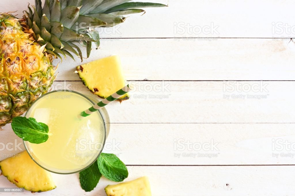 Pineapple juice, top view, side border on white wood stock photo