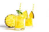 Pineapple juice with marijuana with fruit slices on white flat lay