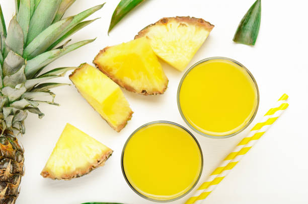 Pineapple juice with pineapple pieces and leaves - summer food composition. Refreshing, dietary, organic fruits. stock photo