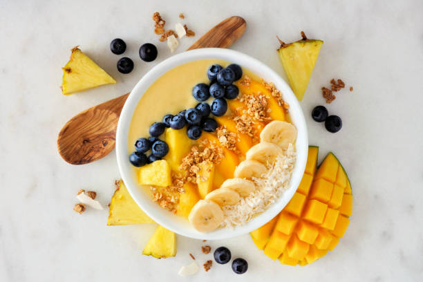 Pineapple, mango smoothie bowl with coconut, bananas, blueberries and granola, above view on a bright background stock photo