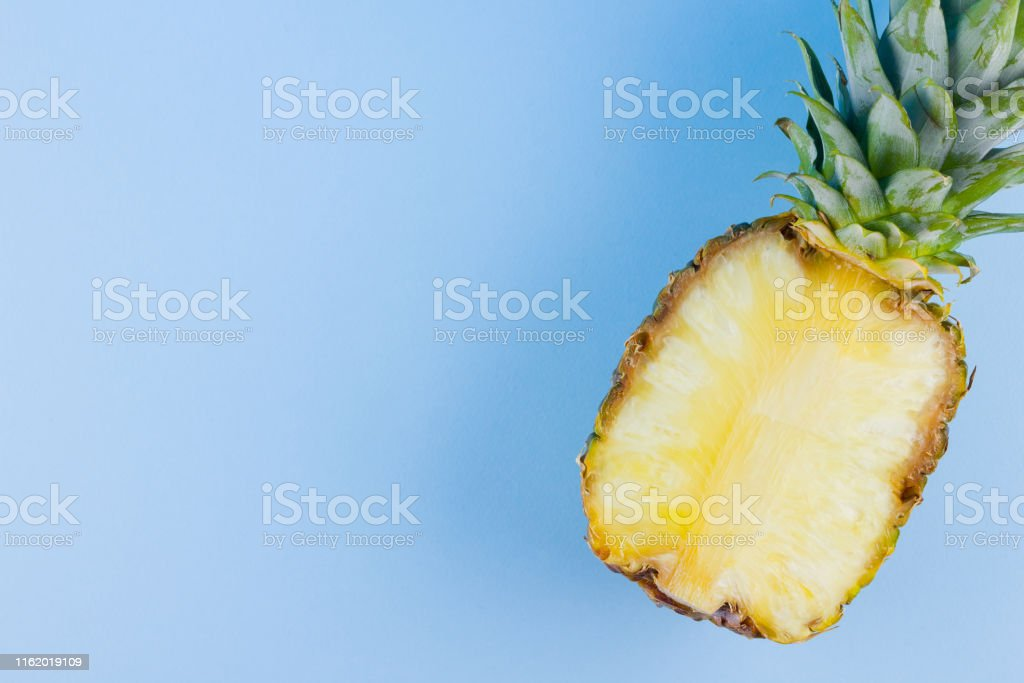 Pineapple on a blue background. Half of pineapple on a pastel...