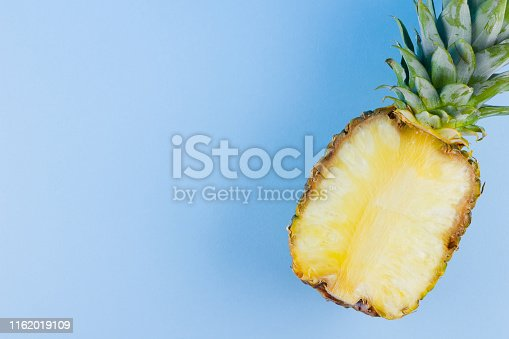 917861766 istock photo Pineapple on a blue background. Half of pineapple on a pastel background. Tropical fruit in a pop art style. Minimalism. Copy space 1162019109