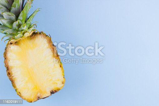 917861766 istock photo Pineapple on a blue background. Half of pineapple on a pastel background. Tropical fruit in a pop art style. Minimalism. Copy space 1162019111