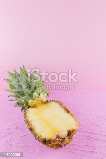 917861766 istock photo Pineapple on a pink background. Half of pineapple on a pastel background. Tropical fruit in a pop art style. Minimalism. Copy space 1162020961