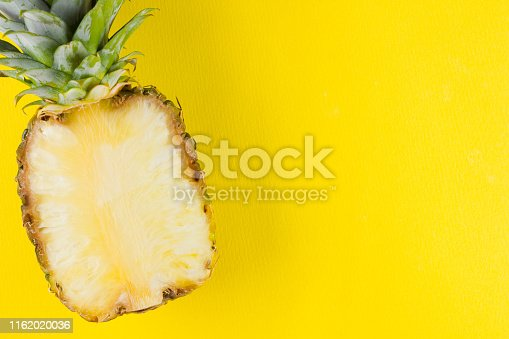 917861766 istock photo Pineapple on a yellow background. Half of pineapple on a pastel background. Tropical fruit in a pop art style. Minimalism. Copy space 1162020036