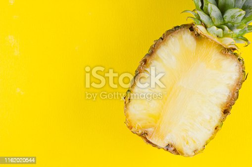 917861766 istock photo Pineapple on a yellow background. Half of pineapple on a pastel background. Tropical fruit in a pop art style. Minimalism. Copy space 1162020544