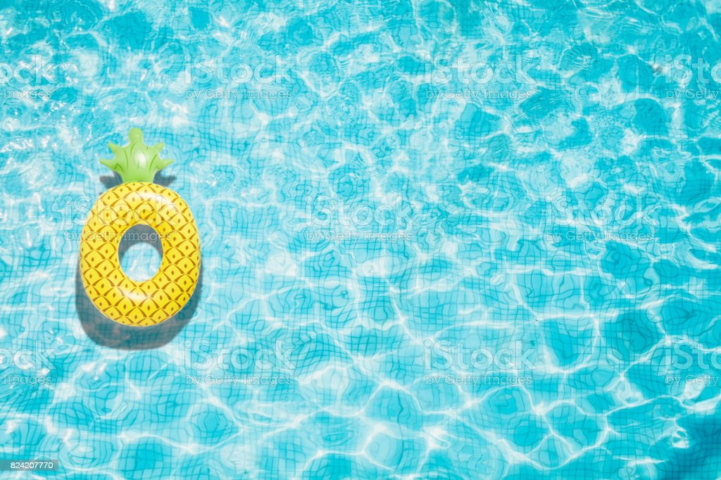 Pineapple pool float, ring floating in a refreshing blue swimming pool stock photo