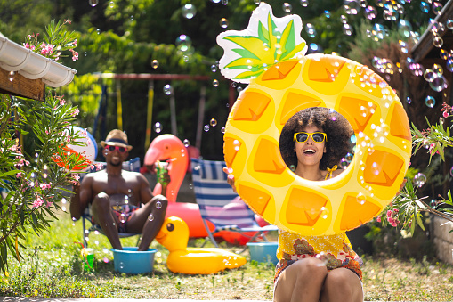 Young woman having fun during his holiday at home, boyfriend sitting on a lounge chair in the background