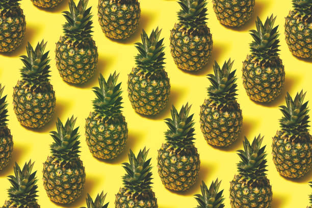 Pineapple repetitive flat lay on yellow background stock photo